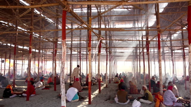 suns rays slant through ricketty wooden scaffolding as devotees sit on ground below around fires, involved in religious ritual. kumbh mela, india - scaffolding stock videos and b-roll footage