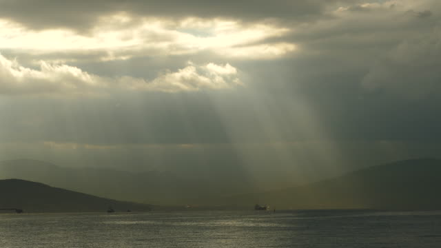 sun's rays through the clouds over the sea and mountains