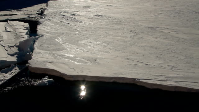 tilt up sun's relfection in water between ice sheets to sun - ice sheet stock videos and b-roll footage
