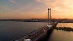 Sunset aerial of autopilot freight trucks riding over bridge.