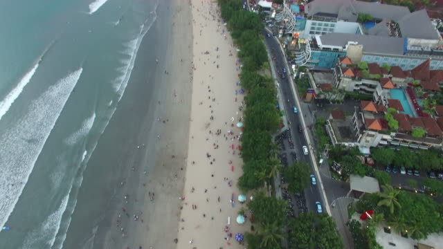 sunset along the crowded beaches of kuta beach, bali. - bali stock videos & royalty-free footage