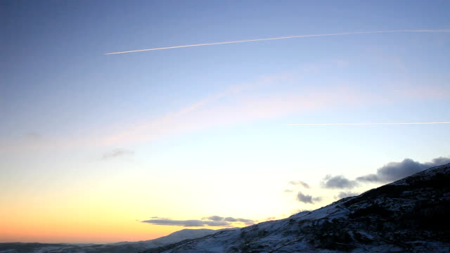 Sunset and airplane contrails