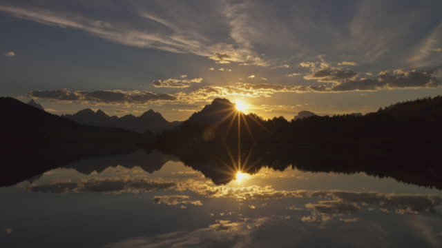 vídeos de stock e filmes b-roll de time lapse long wide shot sunset and clouds behind grand teton with reflections in snake river at oxbow bend in foreground, wyoming - efeito de luz