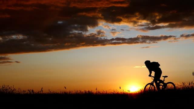 rückansicht der mountainbiker und sonnenuntergang reiten-zeitlupe - motorradfahrer stock-videos und b-roll-filmmaterial