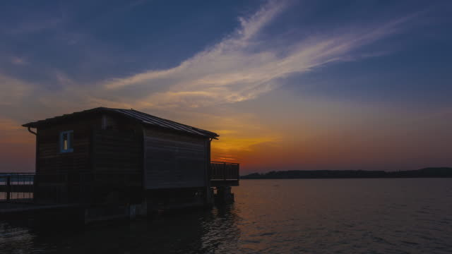 vídeos de stock, filmes e b-roll de t/l sunset at a fisher cabin at lake wörthsee near munich - céu romântico