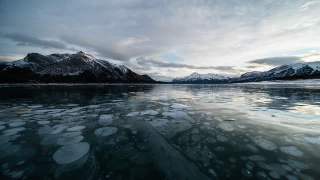 氷の泡と冬のアブラハム湖で夕日 - アルバータ州点の映像素材/bロール