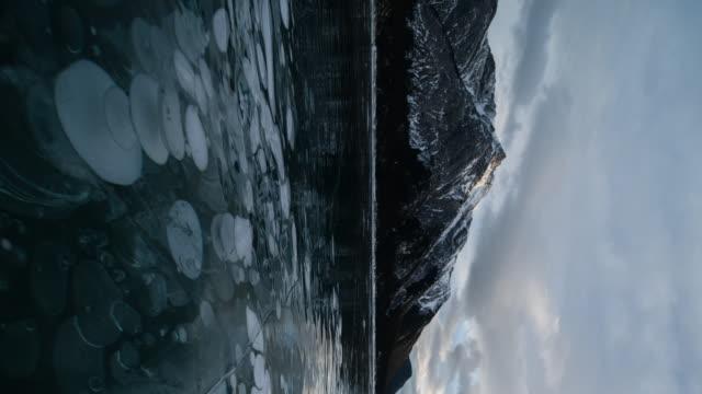 vídeos de stock e filmes b-roll de sunset at abraham lake in winter with ice bubble - congelado