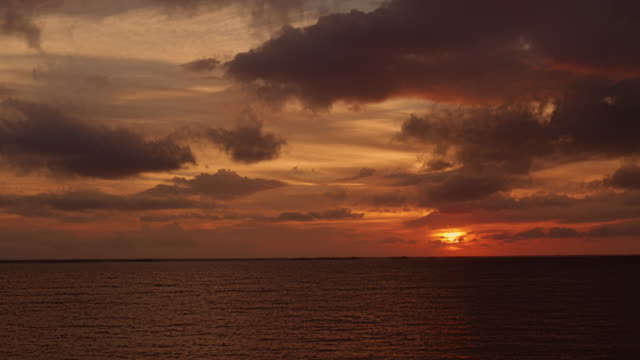 sunset at beach in the bahamas – medium wide shot from great guana cay, abaco - 色が変わる点の映像素材/bロール