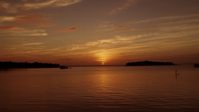 sunset at beach in the bahamas – wide shot from great guana cay, abaco - 色が変わる点の映像素材/bロール