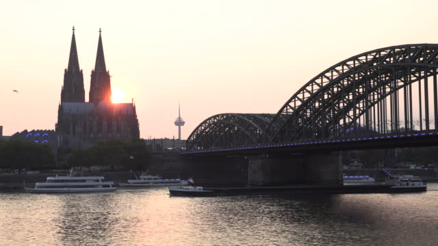 stockvideo's en b-roll-footage met sunset at cathedral of cologne blue lights shining on hohenzollern bridge and ships passing by - sint petersburg rusland