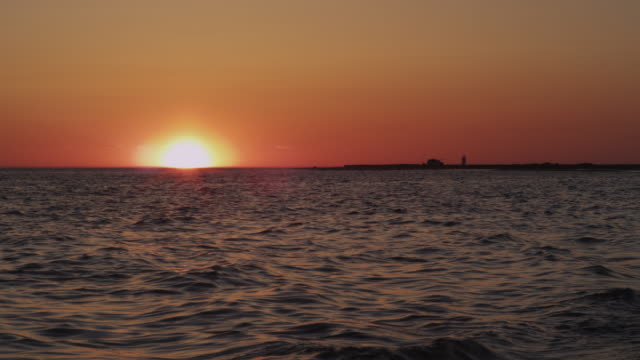 stockvideo's en b-roll-footage met sunset at herring cove on cape cod's national seashore with lighthouse and ocean waves in real time. - zeegezicht