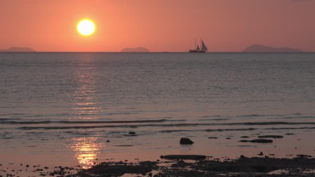 Sunset at sea with sailboat