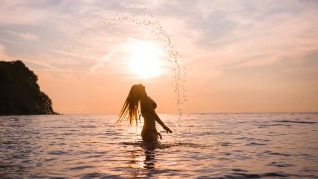 sunset at sea, woman having fun on tropical vacation, splashing water with hair - idyllic stock videos & royalty-free footage