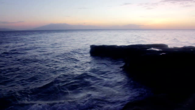 sunset at the beach with big rocks on the foreground - batangas province stock videos and b-roll footage