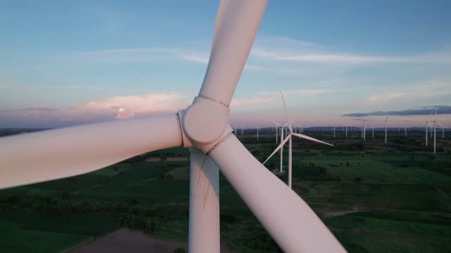 sunset at wind turbine power generator farm. - panning stock videos & royalty-free footage