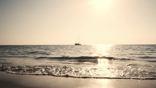 sunset beach waves seascape with sailboat - 40 seconds or greater stock videos & royalty-free footage