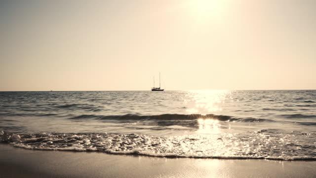 sunset beach vågor seascape med segelbåt - 40 sekunder eller längre bildbanksvideor och videomaterial från bakom kulisserna