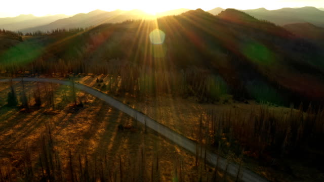 sunset beams over road and mountains by drone - horizon over land stock videos & royalty-free footage