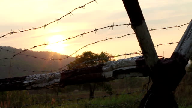 sunset behind barbed wire and mountian - fence stock videos & royalty-free footage