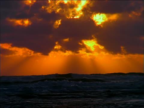 vídeos de stock, filmes e b-roll de sunset behind clouds in orange sky over breaking waves - céu romântico