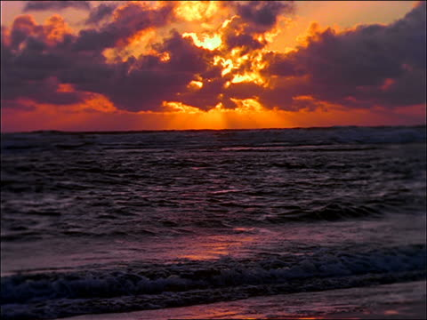 vídeos de stock, filmes e b-roll de sunset behind clouds over breaking ocean waves - céu romântico