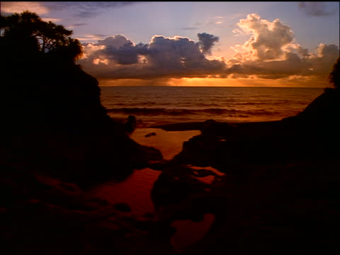 vídeos de stock e filmes b-roll de sunset behind clouds over ocean with beach + silhouetted rock formations in foreground / maui, hawaii - vista do mar