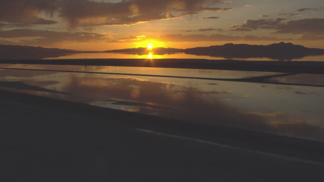 Sunset behind mountain with reflection on Great Salt Lake