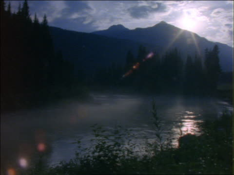 sunset behind mountains with misty lake in foreground - pinacee video stock e b–roll