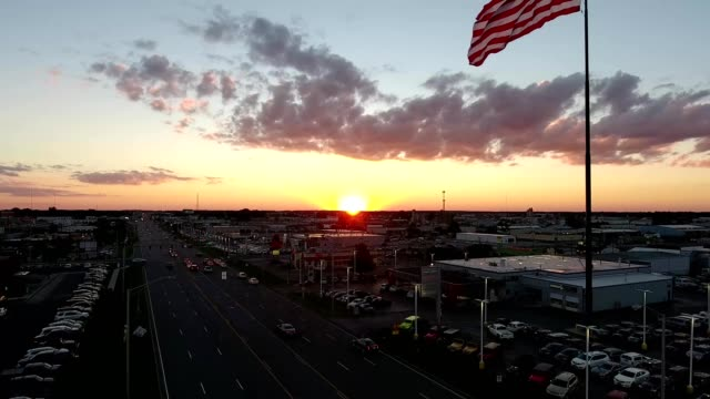 sunset behind the american flag in fort wayne - indiana stock videos & royalty-free footage
