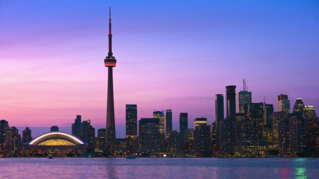 t/l sunset behind the toronto skyline, rogers center, cn tower and lake ontario / toronto, ontario, canada - toronto stock videos & royalty-free footage
