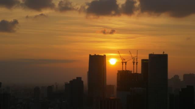 stockvideo's en b-roll-footage met sunset between buildings - crane construction machinery
