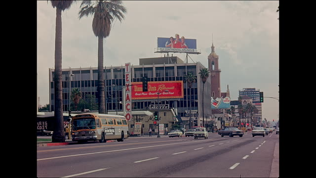 sunset blvd in hollywood in 1974 near highland ave intersection looking east towards blessed sacrament jesuit parish church with gas station in foreground - sunset boulevard stock-videos und b-roll-filmmaterial