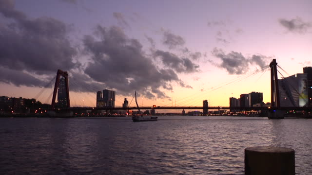sunset by the river in rotterdam, with ships passing under the willemsbrug - schiffsfracht stock-videos und b-roll-filmmaterial