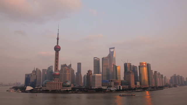 sunset city skyline with the oriental pearl tower, huangpu river, pudong district, shanghai, china, asia - the bund stock videos & royalty-free footage