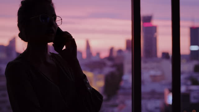 sunset cityscape in office windows. elegant businesswoman's silhouette making a call - sitting stock videos & royalty-free footage