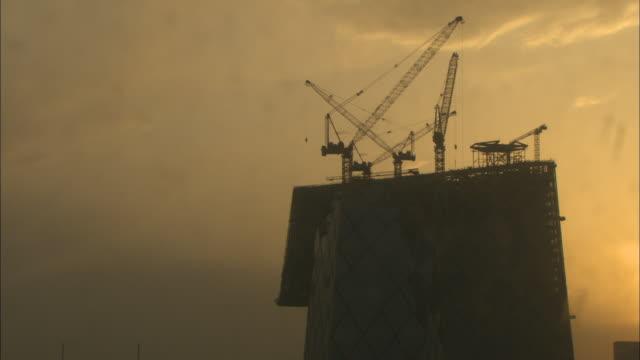 ws sunset clouds behind multiple cranes sitting atop building under construction, guilin, guangxi zhuang autonomous region, china - guangxi zhuang autonomous region china stock videos & royalty-free footage