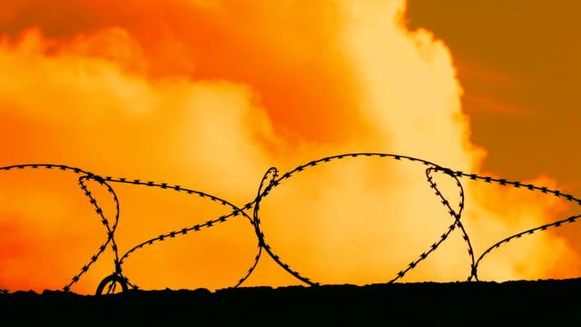 有刺鉄線 (時間経過) の後ろに夕焼け雲 - コンクリート点の映像素材/bロール
