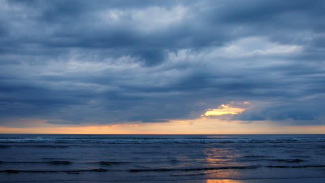 sunset cloudscape over a pristine new zealand beach - dramatic sky stock videos & royalty-free footage