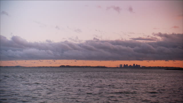 a sunset colors the sky over boston. - north atlantic ocean stock videos & royalty-free footage