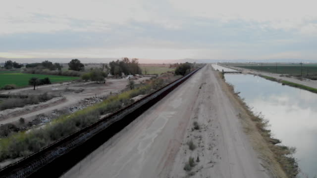 a sunset drone view of the international border wall dividing arizona and california from mexico - international border stock videos & royalty-free footage