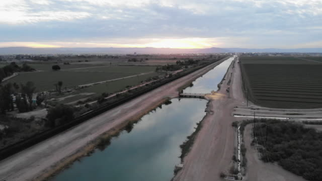 a sunset drone view of the international border wall dividing arizona and california from mexico - canal stock videos & royalty-free footage