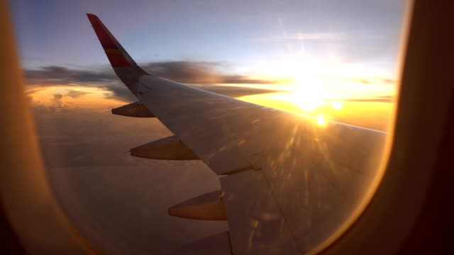 sunset flight and twilight sky with aircraft wing from an airplane window - aircraft wing stock videos & royalty-free footage