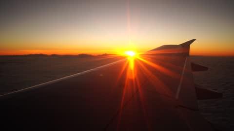 vidéos et rushes de vol de coucher du soleil avec l'aile d'avion d'une fenêtre d'avion - pilote
