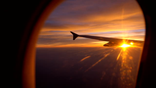 vídeos de stock e filmes b-roll de sunset flight with aircraft wing from an airplane window - crepúsculo