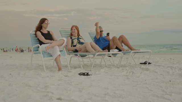 Sunset Florida beach family sitting sun chairs summer woman man