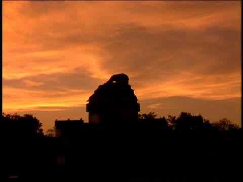 vídeos de stock e filmes b-roll de a sunset illuminates an ancient mayan observatory. - astronomia
