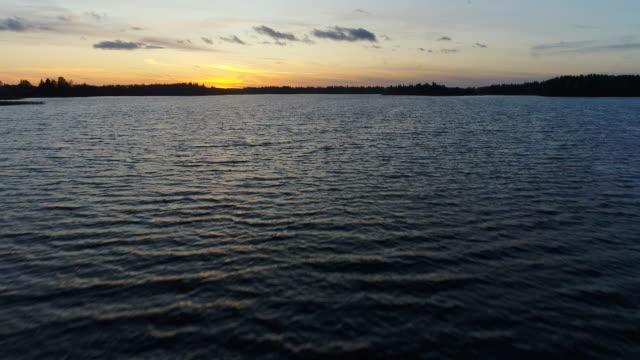 stockvideo's en b-roll-footage met zonsondergang in adamovas lake letland - zomerzonnewende