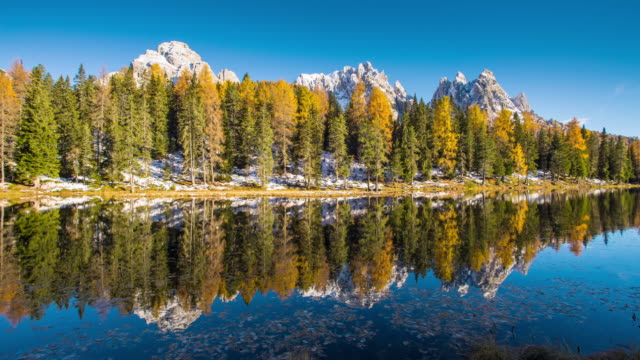 Sunset in Antorno lake with Cadini of Misurina reflex in the lake, Sexten Dolomites Natural Park in autumn