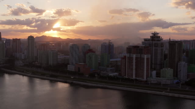sunset in pyongyang seen from yanggakdo hotel. skyline at taedong river with smoke from a nearby coal power plant. - spoonfilm stock videos and b-roll footage