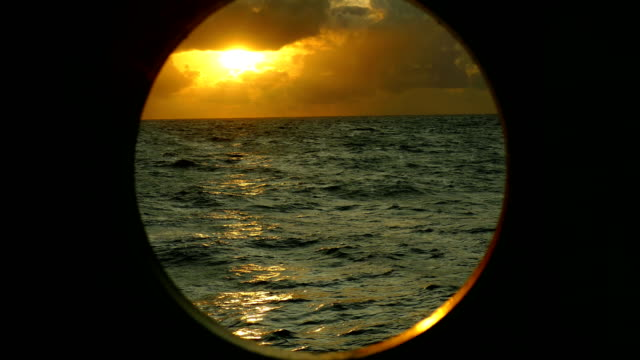 sunset in the atlantic ocean in the porthole of a ship - porthole stock videos & royalty-free footage
